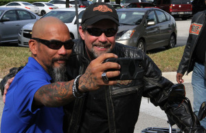U.S. Marine veteran Raymond Andalio poses with Bill Davidson, great-grandson of Harley-Davidson co-founder William A. Davidson, after learning he would receive a 2015 Harley-Davidson motorcycle.