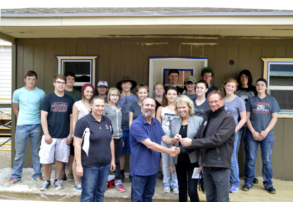 Sturgis Brown High School geometry-in-construction instructor Jon Swan, second from left, hands over the keys for the camping cabins to Buffalo Chip Campground owner Rod Woodruff for whom the students built the two structures. Also pictured, in the front, are Deb Cano, left, SBHS geometry teacher, and Nyla Griffith, media/public relations for Buffalo Chip. Also present for the key exchange were the SBHS students who built the cabins. (Photo by Kris Hubbard/Meade School District)